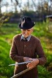 Fazendeiro idoso que aponta a foice Fotografia de Stock Royalty Free