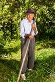 Fazendeiro idoso que usa a foice para segar a grama fotografia de stock royalty free