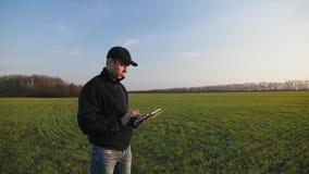 Fazendeiro masculino com tablet pc portátil em um campo de trigo video estoque