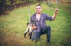 Fazendeiro masculino que guarda a cabra Fotografia de Stock Royalty Free