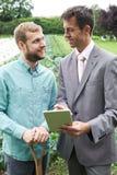 Fazendeiro Meeting With Businessman no campo imagem de stock royalty free