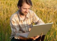 Fazendeiro moderno no campo de trigo com portátil Fotografia de Stock Royalty Free