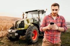 Fazendeiro moderno que usa o smartphone para controlar a colheita orgânica - conceito moderno da agricultura imagens de stock royalty free