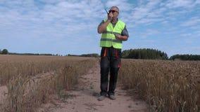 Fazendeiro no campo de cereal com Walkietalkie vídeos de arquivo