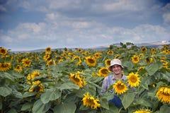 Fazendeiro no campo do girassol Imagens de Stock Royalty Free