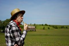 Fazendeiro no chapéu de palha com a tubulação da espiga de milho Imagens de Stock