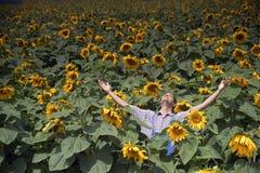Fazendeiro nos braços do campo do girassol espalhados para fora Fotografia de Stock