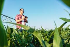 Fazendeiro novo moderno feliz que inspeciona seus campos com um zangão fotografia de stock