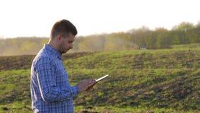 Fazendeiro novo que guarda a tabuleta na frente do trator no campo Trabalhador agrícola sazonal Ecologia do conceito, transporte vídeos de arquivo