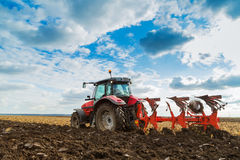 Fazendeiro que ara o campo de restolho com trator vermelho Imagens de Stock