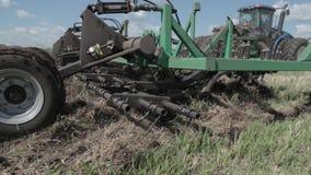 Fazendeiro que ara o campo Pequena escala que cultiva com trator e arado no campo, cultivando o trator no campo Exploração agríco video estoque