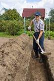 Fazendeiro que escava a terra para construir uma cama profunda de Fotos de Stock
