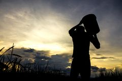 Fazendeiro que leva uma cubeta imagem de stock