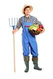 Fazendeiro que prende um pitchfork e uma cubeta Imagem de Stock Royalty Free