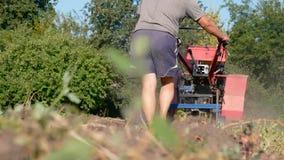 Fazendeiro que recolhe a batata usando a ceifeira video estoque