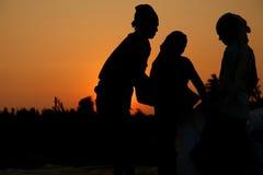 Fazendeiro que trabalha em um campo do arroz no por do sol Fotografia de Stock