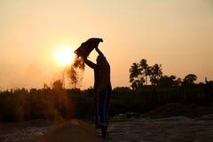 Fazendeiro que trabalha em um campo do arroz no por do sol Imagem de Stock