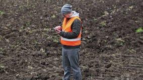 Fazendeiro que usa o PC da tabuleta no campo arado video estoque