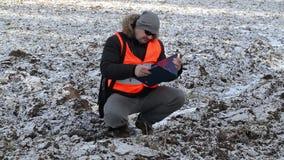 Fazendeiro que usa o PC da tabuleta no campo arado, congelado com neve no inverno video estoque