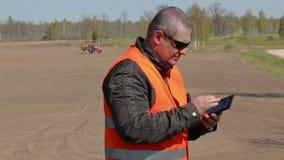 Fazendeiro que usa o PC da tabuleta no campo onde a grade do trator a terra video estoque