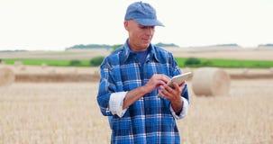 Fazendeiro que usa a tabuleta digital ao examinar o campo filme