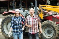 Fazendeiros idosos e novos que trabalham na maquinaria Foto de Stock