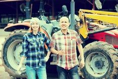 Fazendeiros idosos e novos que trabalham na maquinaria Imagem de Stock Royalty Free