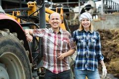 Fazendeiros maduros e novos que trabalham na maquinaria Fotos de Stock