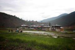 Fazendeiros no campo de almofada perto de uma vila foto de stock royalty free