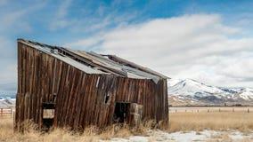 Fazendeiros que constroem para fora com montanhas cobertos de neve e o céu nebuloso Foto de Stock Royalty Free