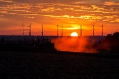 Fazendeiros que trabalham com um trator no campo no por do sol com as turbinas eólicas no fundo foto de stock royalty free