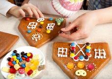 Fazendo a casa de pão-de-espécie do Natal junto Foto de Stock Royalty Free