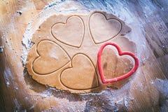 Fazendo a cookie do coração do pão-de-espécie do Natal Fotografia de Stock Royalty Free