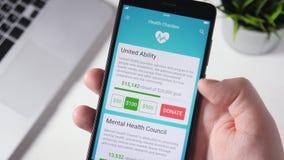 Fazendo a doação da caridade à organização de saúde usando Smartphone App video estoque