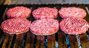 Fazendo e grelhando rissóis de carne do Hamburger no carvão grelhe Foto de Stock Royalty Free