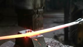 Fazendo a espada fora do metal na forja Mão do ` s do homem do close up usando o martelo pneumático para dar forma ao metal quent filme