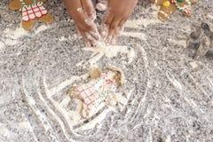 Fazendo homens de pão-de-espécie sobre o branco da farinha de trigo foto de stock royalty free