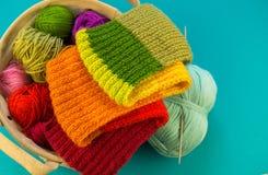 Fazendo malha um fundo do azul do lenço e do chapéu do arco-íris imagem de stock royalty free
