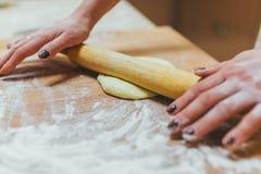 Fazendo a massa pelas mãos fêmeas no fundo de madeira da tabela imagens de stock