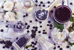 Fazendo o fruto bloqueie o conceito com açúcar, a baga fresca, os frascos de vidro, a colher e as rosas na tabela Imagens de Stock Royalty Free
