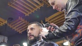 Fazendo o olhar do cabelo mágico Homem farpado novo que obtém o corte de cabelo com a lâmina reta da borda pelo cabeleireiro ao s vídeos de arquivo