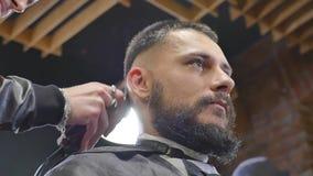 Fazendo o olhar do cabelo mágico Homem farpado novo que obtém o corte de cabelo com a lâmina reta da borda pelo cabeleireiro ao s video estoque