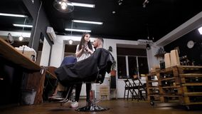 Fazendo o penteado à moda na barbearia elegante Moderno masculino e barbeiro fêmea vídeos de arquivo