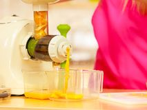 Fazendo o suco de laranja na máquina do juicer na cozinha Foto de Stock