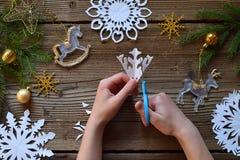 Fazendo os flocos de neve de papel com suas próprias mãos Children& x27; s DIY Conceito do Feliz Natal e do ano novo Etapa 2 Cort imagens de stock royalty free