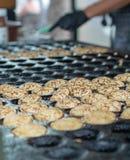 Fazendo panquecas pequenas, poffertjes holandeses tradicionais na rua miliampère imagens de stock royalty free