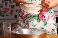 Fazendo a pizza pelas mãos fêmeas na mesa de cozinha Imagens de Stock