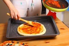 Fazendo a pizza pelas mãos fêmeas na mesa de cozinha Imagem de Stock Royalty Free