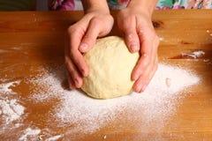Fazendo a pizza pelas mãos fêmeas na mesa de cozinha Fotografia de Stock Royalty Free