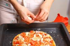 Fazendo a pizza pelas mãos fêmeas na mesa de cozinha Fotos de Stock